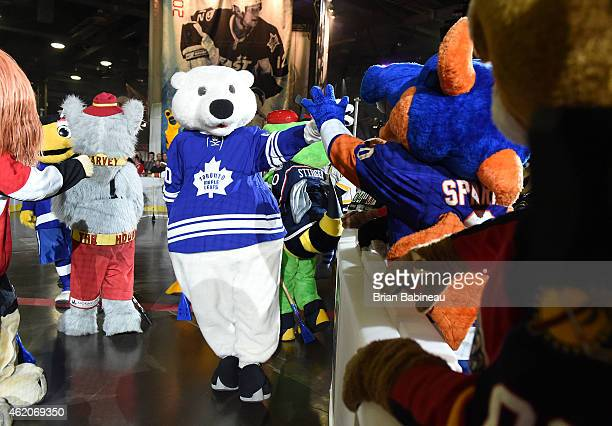 Carlton the Bear of the Toronto Maple Leafs high fives Sparky the Dragon of the New York Islanders during the mascot showdown as part of the 2015 NHL...