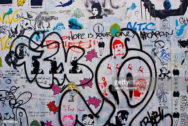 Graffiti artists leave their mark on a building wall in a city lane.