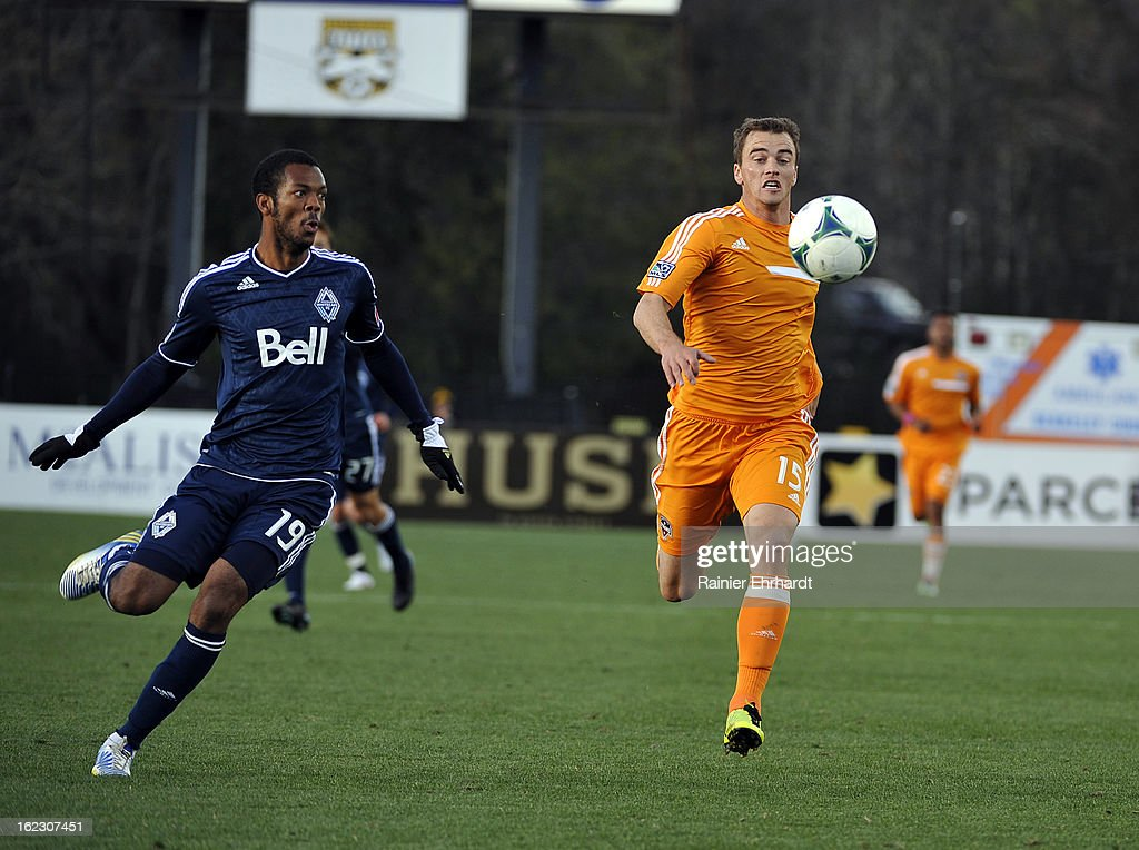 Carlyle Mitchell #19 of the Vancouver Whitecaps FC and Cam Weaver #15 of the Houston Dynamo battle for the ball during the first half of a game at Blackbaud Stadium on February 20, 2013 in Charleston, South Carolina.