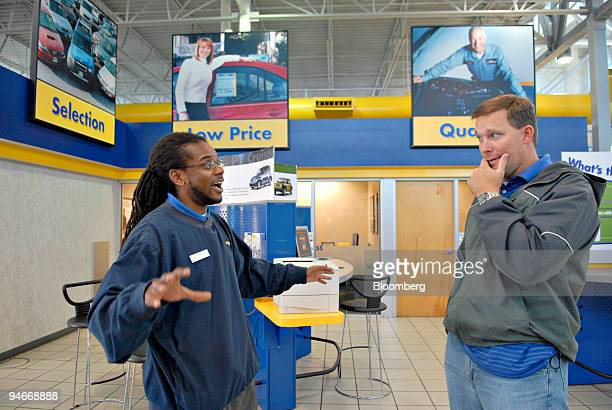 CarMax salesman Will Hyde talks with customer Stacy Wilson about the status of his newly purchased car at a CarMax dealership in Norcross Georgia US...