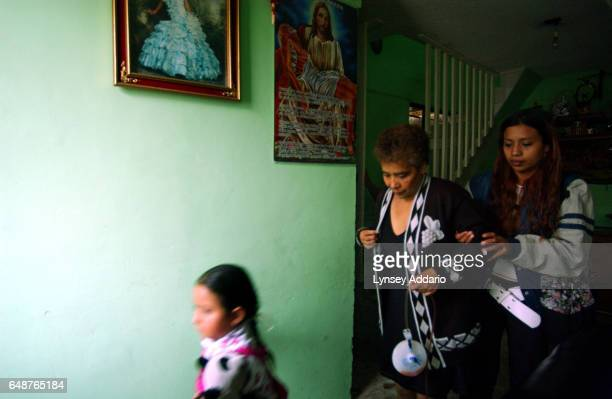 Carmela Estrela is assisted by her daughter as she walks through her house on the way to the hospital for a check up eight days after an operation to...