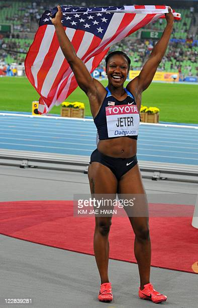 US Carmelita Jeter celebrates victory after competing in the women's 100 metres final at the International Association of Athletics Federations World...