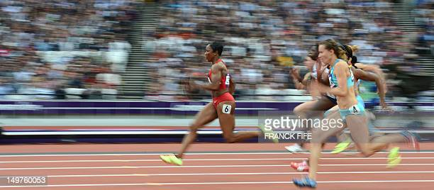 US' Carmelita Jeter competes with Kazakhstan's Olga Bludova in the women's 100m heats at the athletics event during the London 2012 Olympic Games on...