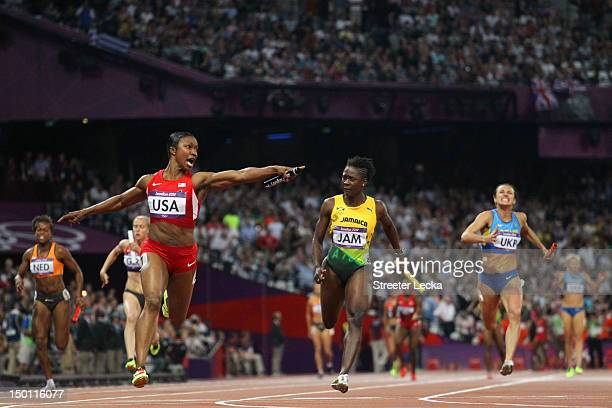 Carmelita Jeter of the United States celebrates winning gold ahead of Kerron Stewart of Jamaica and Elyzaveta Bryzgina of Ukraine during the Women's...