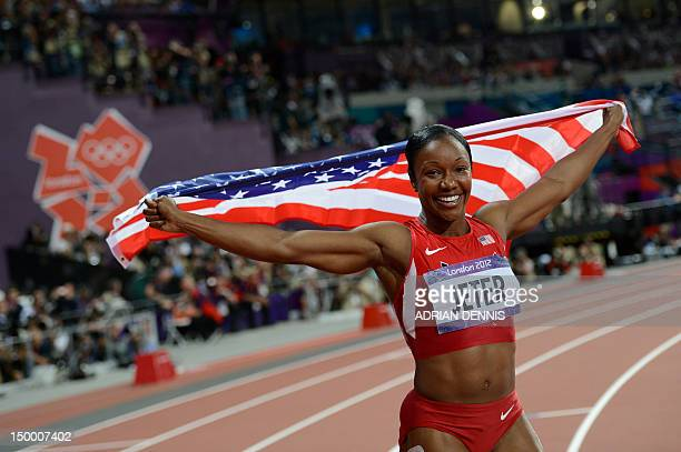 US' Carmelita Jeter waves her national flag as she celebrates winning the bronze medal in the women's 200m final at the athletics event of the London...