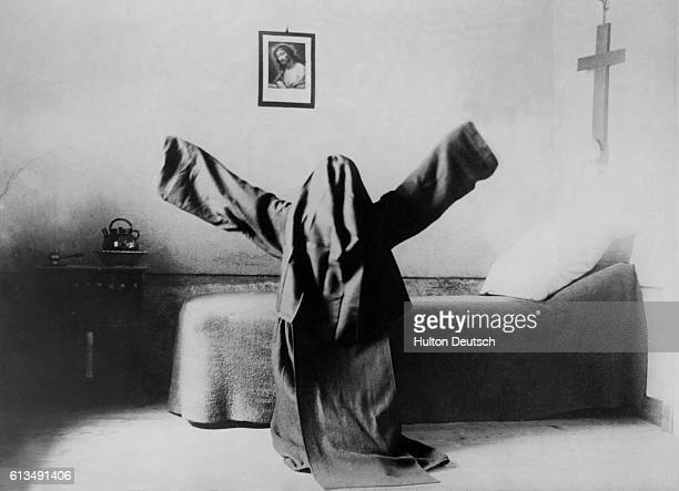 Carmelite nun kneels by her bed with her arms outstretched.