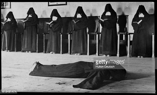 Carmelite nun lies prostrate on the floor to expiate her sins whilst her sisters read over her. 1904.