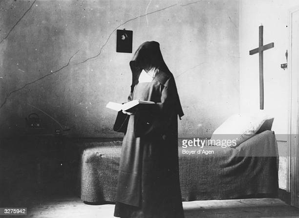 Carmelite nun reading a book in the cell furnished only with a bed.