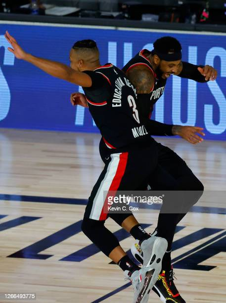 Carmelo Anthony and CJ McCollum of the Portland Trail Blazers celebrate a three point basket against the Memphis Grizzlies during the fourth quarter...