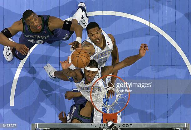 Carmelo Anthony and Marcus Camby of the Denver Nuggets reach for a rebound against Ervin Johnson of the Minnesota Timberwolves in game four of the...