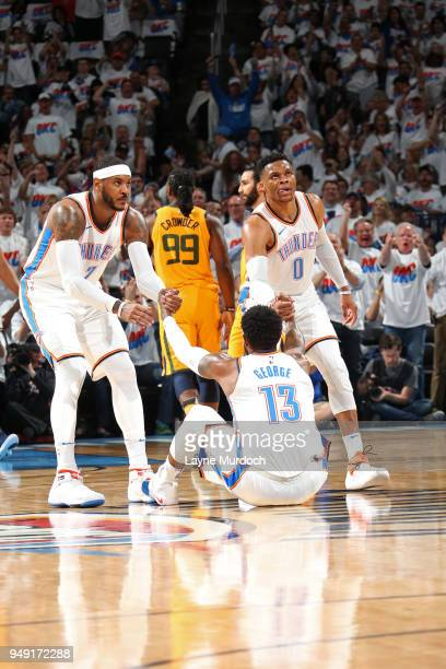 Carmelo Anthony and Russell Westbrook help up Paul George of the Oklahoma City Thunder against the Utah Jazz in Game Two of Round One of the 2018 NBA...