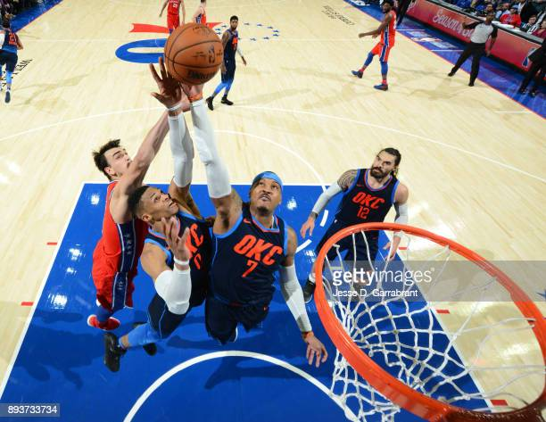 Carmelo Anthony and Russell Westbrook of the Oklahoma City Thunder goes up for the rebound against the Philadelphia 76ers at Wells Fargo Center on...