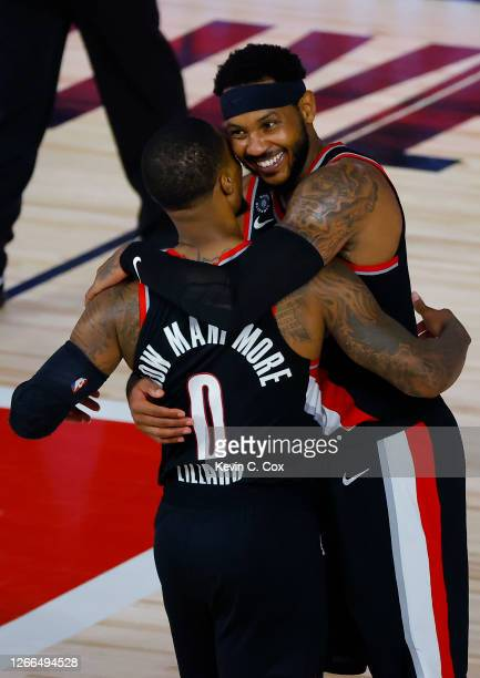 Carmelo Anthony hugs Damian Lillard of the Portland Trail Blazers after a win against the Memphis Grizzlies during the Western Conference play-in...