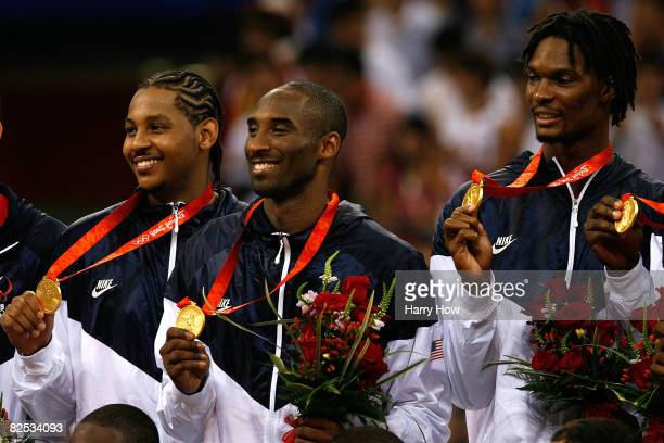 Carmelo Anthony, Kobe Bryant and Chris Bosh of the United States hold their gold medals after defeating Spain 118-107 in the gold medal game during...