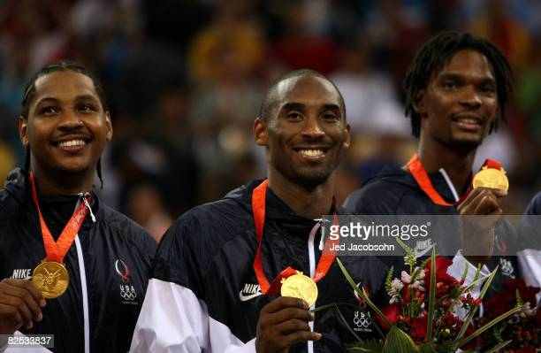 Carmelo Anthony, Kobe Bryant and Chris Bosh of the United States stand on the podium during the national anthem after defeating Spain in the gold...