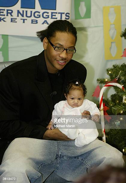Carmelo Anthony of Denver Nuggets holds a baby at the Family Resource Center December 15 2003 in Aurora Colorado NOTE TO USER User expressly...