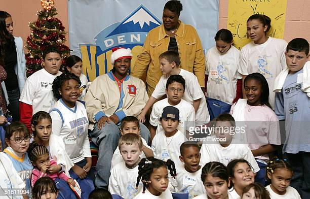 Carmelo Anthony of the Denver Nuggets and his mother Mary pose for a picture with children during A Very Melo Christmas Party on December 1 2004 at...