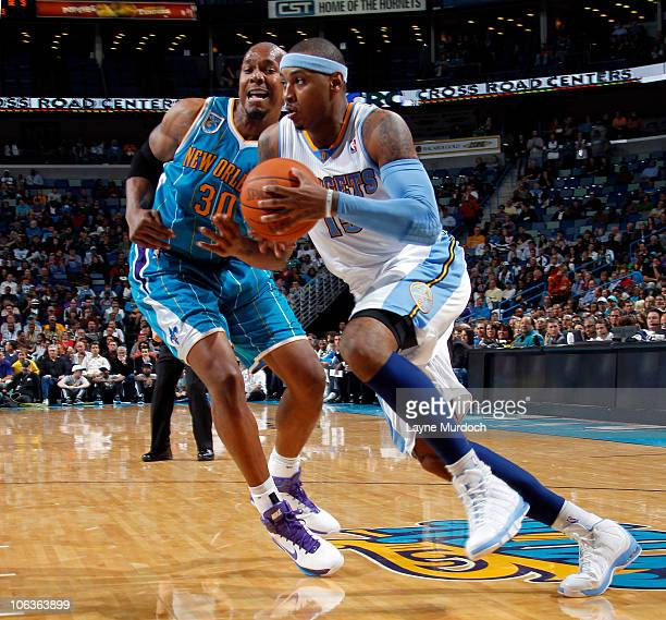 Carmelo Anthony of the Denver Nuggets drives on David West of the New Orleans Hornets on October 29 2010 at the New Orleans Arena in New Orleans...