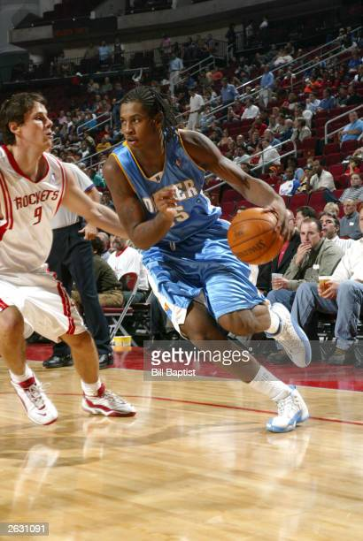 Carmelo Anthony of the Denver Nuggets drives past Bostjan Nachbar of the Houston Rockets October 22 2003 at the Toyota Center in Houston Texas NOTE...