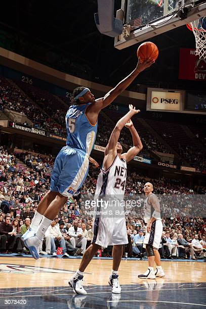 Carmelo Anthony of the Denver Nuggets drives to the basket against Richard Jefferson of the New Jersey Nets March 10 2004 at Continental Airlines...