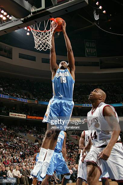 Carmelo Anthony of the Denver Nuggets dunks past Derrick Coleman of the Philadelphia 76ers on December 12, 2003 at the Wachovia Center in...