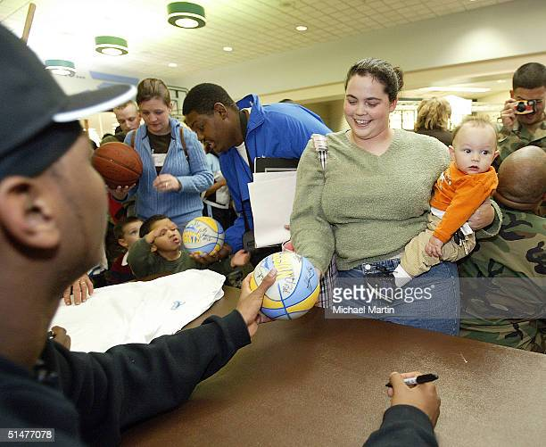 Carmelo Anthony of the Denver Nuggets gives an autograph to Elaine Mott and her baby Aiden while visiting soldiers at Ft Carson on October 13 2004 in...