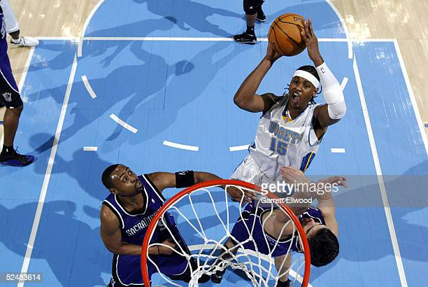 Carmelo Anthony of the Denver Nuggets goes to the basket against Peja Stojakovic of the Sacramento Kings on March 26, 2005 at the Pepsi Center in...