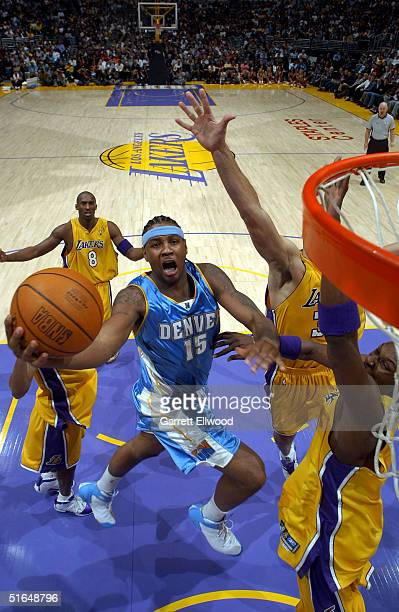 Carmelo Anthony of the Denver Nuggets goes to the hoop past Chris Mihm Lamar Odom and Kobe Bryant of the Los Angeles Lakers on November 2 2004 at the...