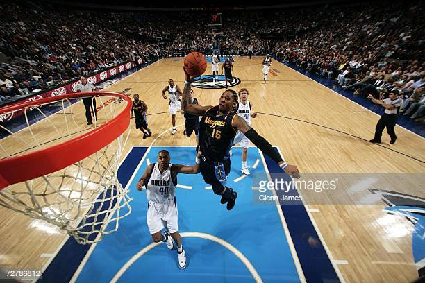 Carmelo Anthony of the Denver Nuggets goes up for a dunk against Devean George of the Dallas Mavericks on December 9 2006 at the American Airlines...