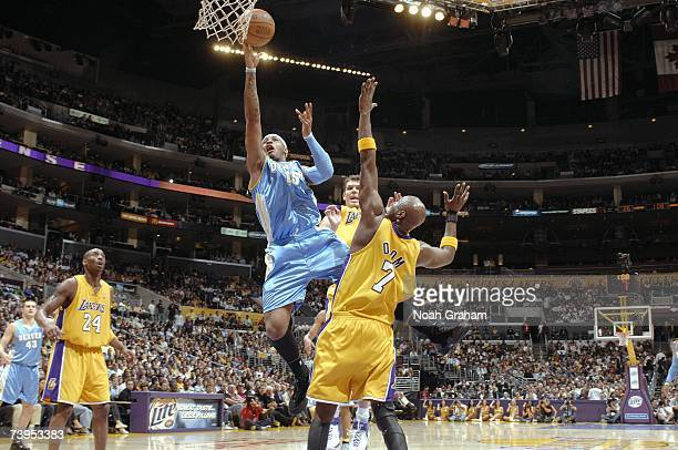 Carmelo Anthony of the Denver Nuggets lays the ball past Luke Walton and Lamar Odom of the Los Angeles Lakers at Staples Center on April 3 2007 in...