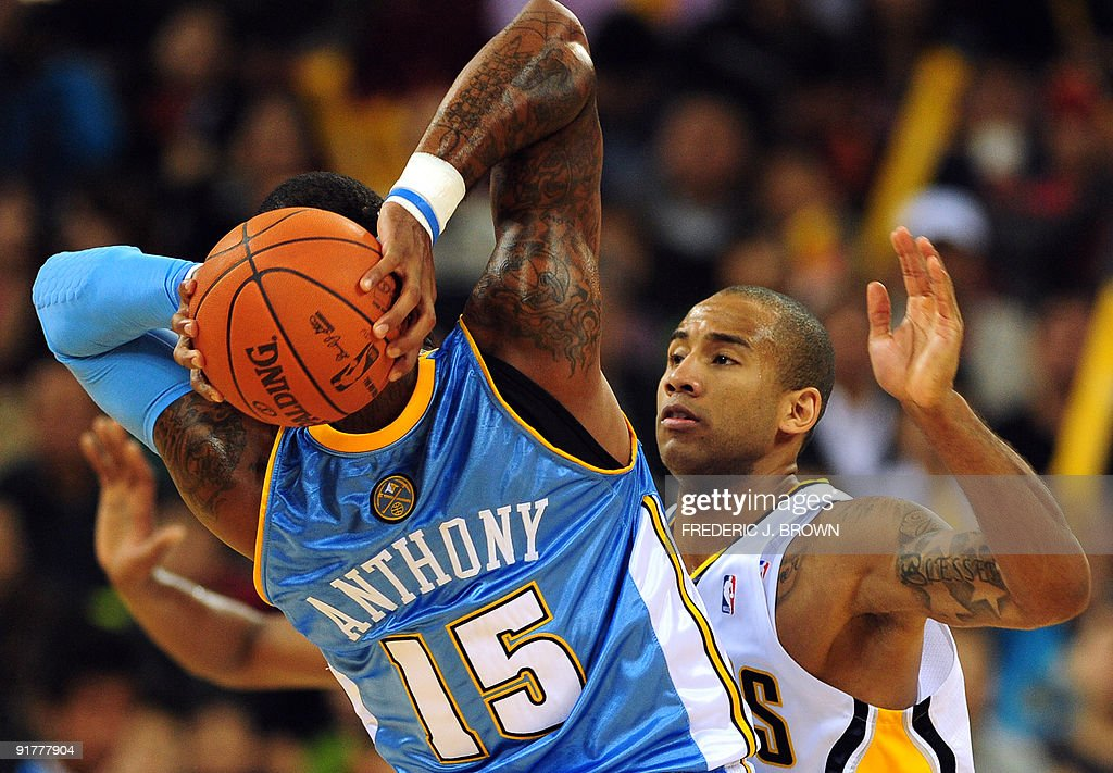 Carmelo Anthony of the Denver Nuggets (L-#15) looks to pass under pressure from Dahntay Jones of the Indiana Pacers (R) during their NBA preseason exhibition game at the Wukesong Arena in Beijing on October 11, 2009. Denver defeated Indiana 128-112. AFP PHOTO/Frederic J. BROWN