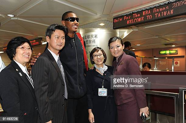 Carmelo Anthony of the Denver Nuggets poses with airport workers upon arrival for the NBA Asia Live Tour at the Taiwan Taoyuan International Airport...