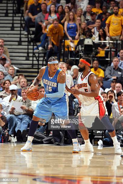 Carmelo Anthony of the Denver Nuggets posts up against Baron Davis of the Golden State Warriors during the game at Oracle Arena on April 10 2008 in...