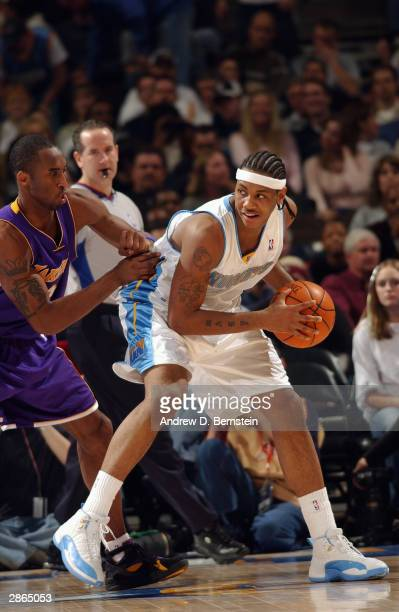 Carmelo Anthony of the Denver Nuggets posts up Kobe Bryant of the Los Angeles Lakers during the game at the Pepsi Center on January 7 2004 in Denver...