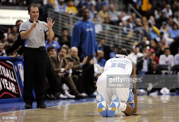 Carmelo Anthony of the Denver Nuggets reacts after pointing out his innocence to referee Tim Donaghy causing Kenyon Martin of the Denver Nuggets to...