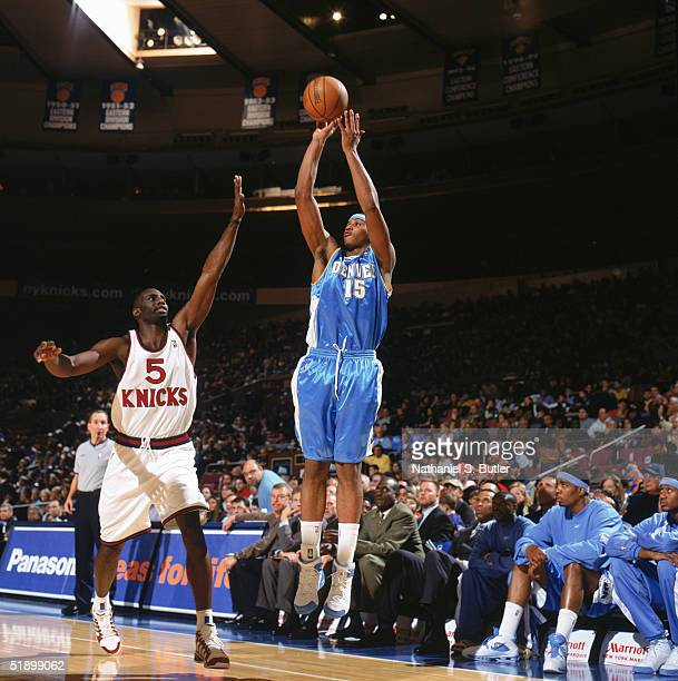 Carmelo Anthony of the Denver Nuggets shoots a jump shot over Tim Thomas of the New York Knicks during a game at Madison Square Garden on December 12...