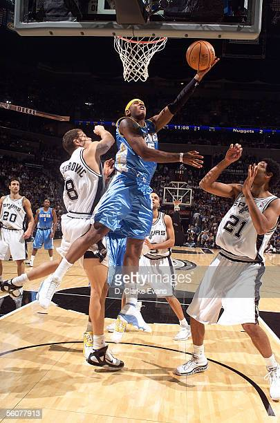 Carmelo Anthony of the Denver Nuggets shoots a reverse layup against Rasho Nesterovic and Tim Duncan of the San Antonio Spurs November 1 2005 at the...