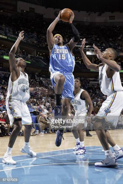 Carmelo Anthony of the Denver Nuggets shoots between Rasual Butler and PJ Brown of the New Orleans/Oklahoma City Hornets on March 18 2006 at the New...