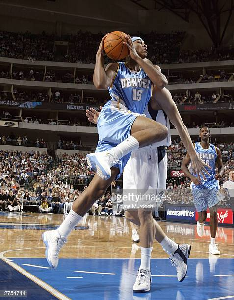 Carmelo Anthony of the Denver Nuggets takes a shot against Dirk Nowitzki of the Dallas Mavericks on November 22 2003 at the American Airlines Center...