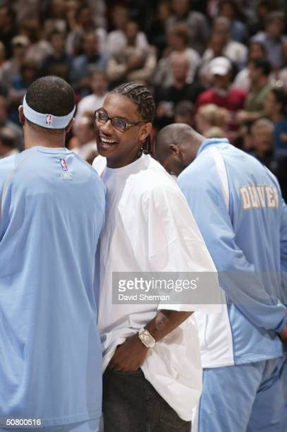 Carmelo Anthony of the Denver Nuggets talks to a teammate before Game five of the Western Conference Quarterfinals during the 2004 NBA Playoffs...