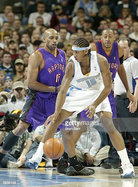 Carmelo Anthony of the Denver Nuggets tries to dribble in on Vince Carter of the Toronto Raptors in the second half of the game on December 30 2003...