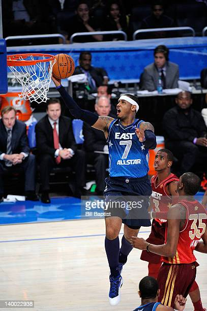 Carmelo Anthony of the Eastern Conference AllStars shoots a layup against Chris Paul and Kevin Durant of the Western Conference AllStars during the...