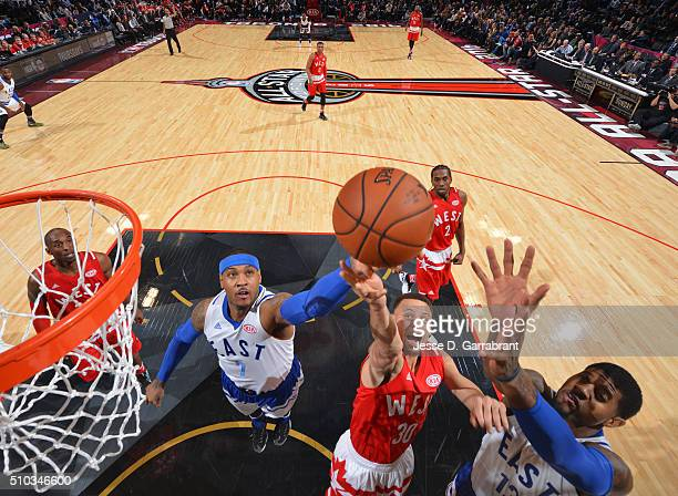 Carmelo Anthony of the Eastern Conference AllStars Stephen Curry and Paul George grabs the rebound during the NBA AllStar Game as part of the 2016...