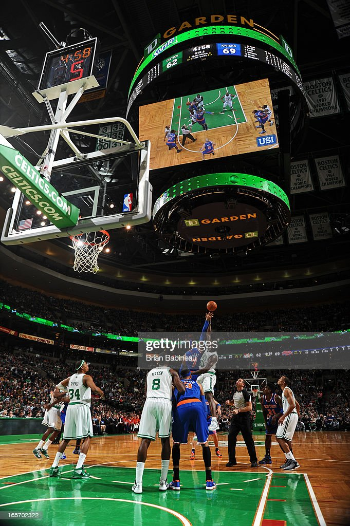 Carmelo Anthony #7 of the New York Knicks and Brandon Bass #30 of the Boston Celtics go up for a jump ball on March 26, 2013 at the TD Garden in Boston, Massachusetts.