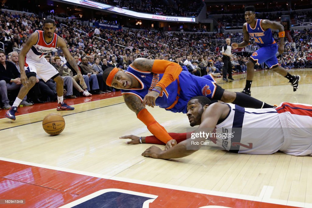 Carmelo Anthony #7 of the New York Knicks and John Wall #2 of the Washington Wizards go after a loose ball during the second half of the Knicks 96-88 win at Verizon Center on March 1, 2013 in Washington, DC.