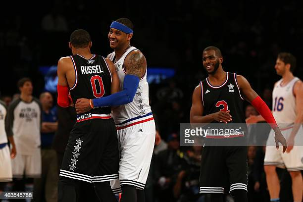Carmelo Anthony of the New York Knicks and the Eastern Conference hugs Russell Westbrook of the Oklahoma City Thunder and the Western Conference...