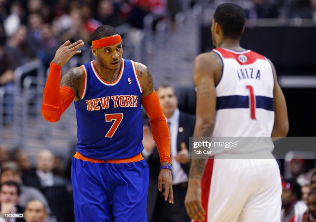 Carmelo Anthony #7 of the New York Knicks celebrates in front of Trevor Ariza #1 of the Washington Wizards after hitting a three point basket during the second half of the Knicks 96-88 win at Verizon Center on March 1, 2013 in Washington, DC.