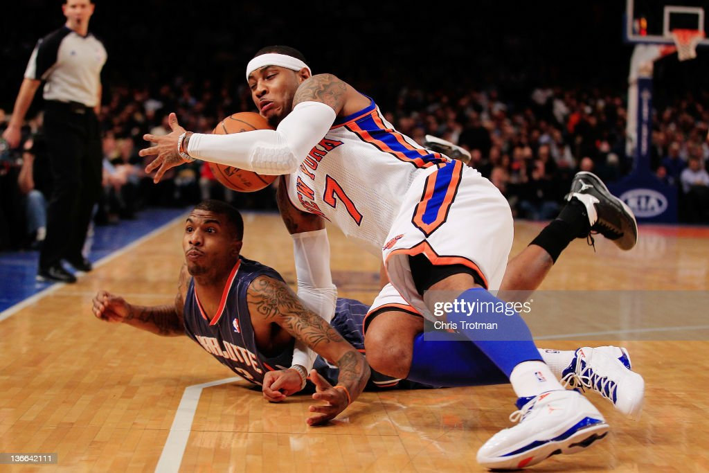 Carmelo Anthony #7 of the New York Knicks competes for a loose ball with Tyrus Thomas #12 of the Charlotte Bobcats at Madison Square Garden on January 9, 2012 in New York City.