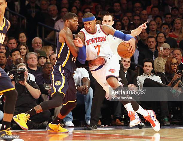 Carmelo Anthony of the New York Knicks dribbles the ball around Paul George of the Indiana Pacers at Madison Square Garden on November 20 2013 in New...