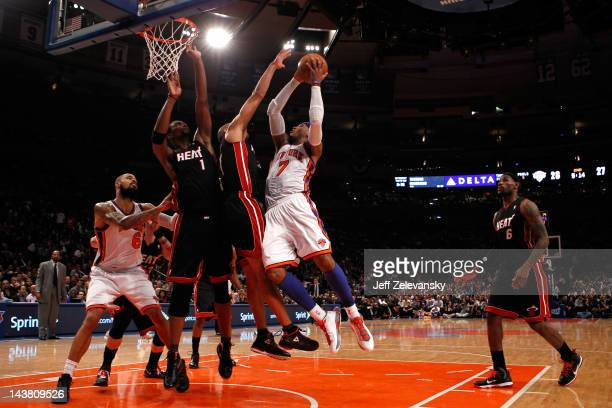 Carmelo Anthony of the New York Knicks drives for a shot attempt in the first half against Shane Battier and Chris Bosh of the Miami Heat in Game...